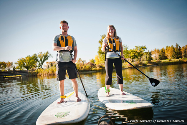 A man and women paddle board in Edmonton River Valley
