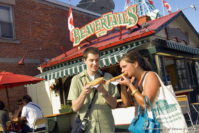 A man and woman enjoy a BeaverTails pastry at the stand on George Street