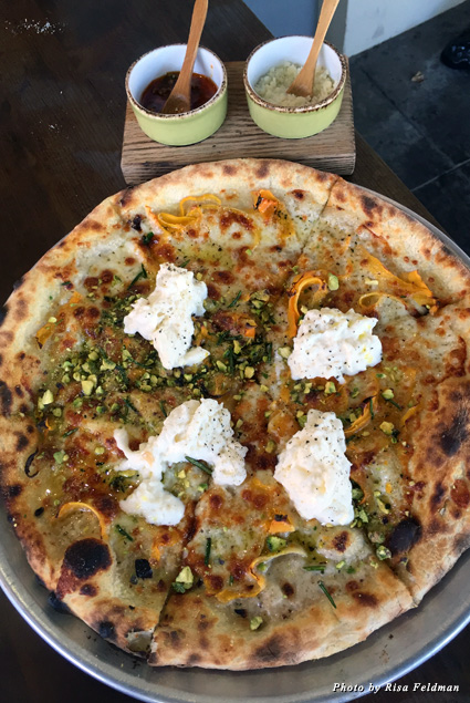 Burrata, provolone, squash blossoms, fried rosemary, shaved pistachio, and orange oil pizza at Wildcraft