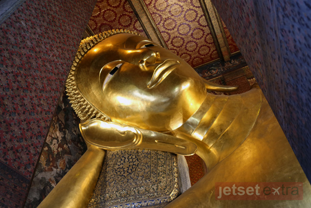 The head, shoulder, and arm of the Reclining Buddha amid the decorative ceiling and walls of its temple