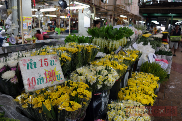 A row of yellow and white flowers for sale at the Chinatown Flower Market