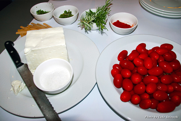 A table of fresh herbs, tomatoes, and cheese