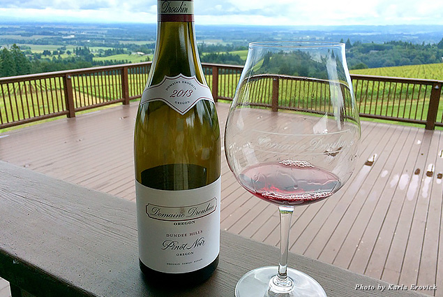 Views of Dundee Hills vineyards behind a bottle and a glass of wine at Domaine Drouhin