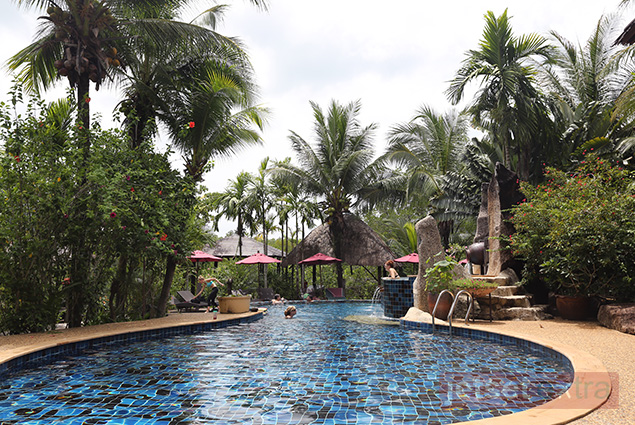 Blue-tiled pool surrounded by tropical plants at Spa Koh Chang