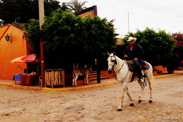 A man sits on his horse on the street in El Quelite