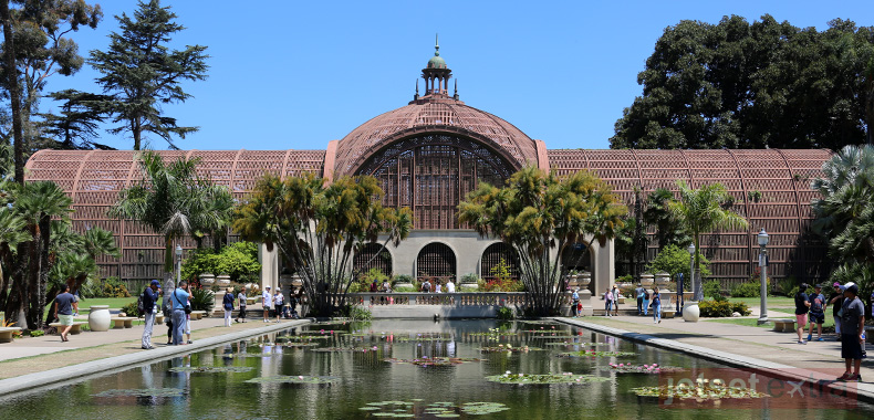 A pond guides guests to the entrance of San Diego's Balboa Park