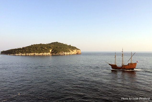A tall ship glides past the island of Lokrum