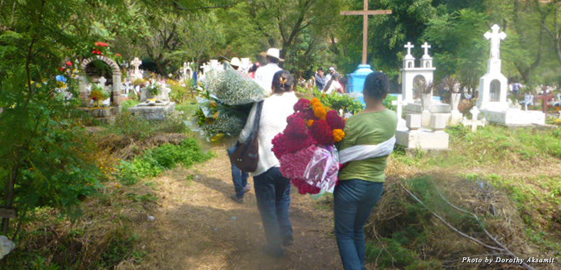 Flowers, candles, and food are carried to the cemetery
