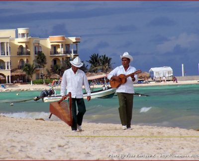 Two musicians walking on the beach hanging their instruments in Playa del Carmen